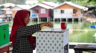 En Thaïlande, une femme vote lors du référendum sur la nouvelle Constitution, le 7 août 2016.