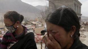 中国青海省玉树地震灾区的一位藏族妇女在为遇难亲人哭泣 2010年4月15日