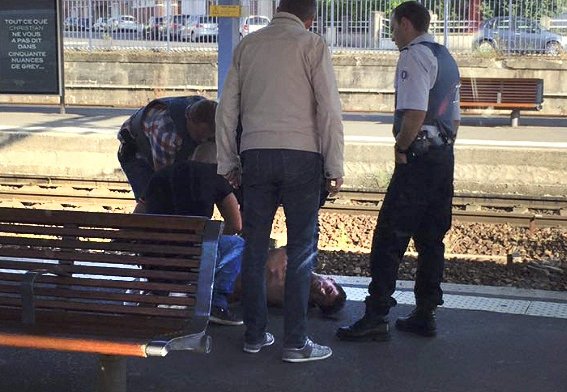 Nghi phạm Ayoub el-Khazzani bị còng tay, trên bến ga thành phố Arras, trong khi cảnh sát điều tra tại hiện trường - REUTERS/Christina Cathleen Coons