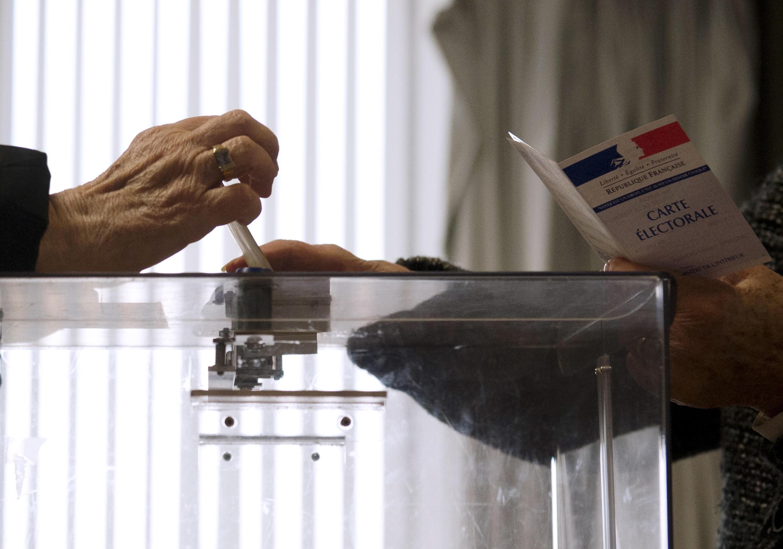 Une femme glisse son bulletin de vote dans l'urne pour le premier tour des élections départementales françaises, à Créteil, au sud de Paris, le dimanche 22 mars 2015.