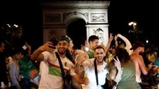 Болельщики сборной Алжира на Елисейских полях вечером 19 июля
