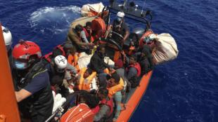Migrantes a la deriva en una embarcación de madera son rescatados por el barco Ocean Viking de la organización humanitaria francesa SOS Mediterranée, frente a la isla de Lampedusa, el 25 de junio de 2020