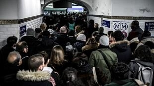 Commuters queue to access the platform of the subway line 1 during a strike of public transports operator SNCF and RATP employees over French government's plan to overhaul the country's retirement system.