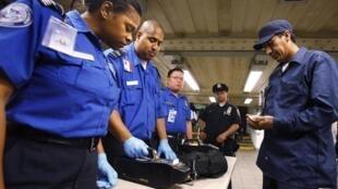 Des officiers de l'administration de sécurité du transport inspectent le sac d'un homme, à l'entrée de la station de métro de Times Square.