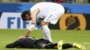 Greece's Giorgios Samaras (top) consoles Ivory Coast's Boubacar Barry after scoring a goal past Barry from a penalty kick