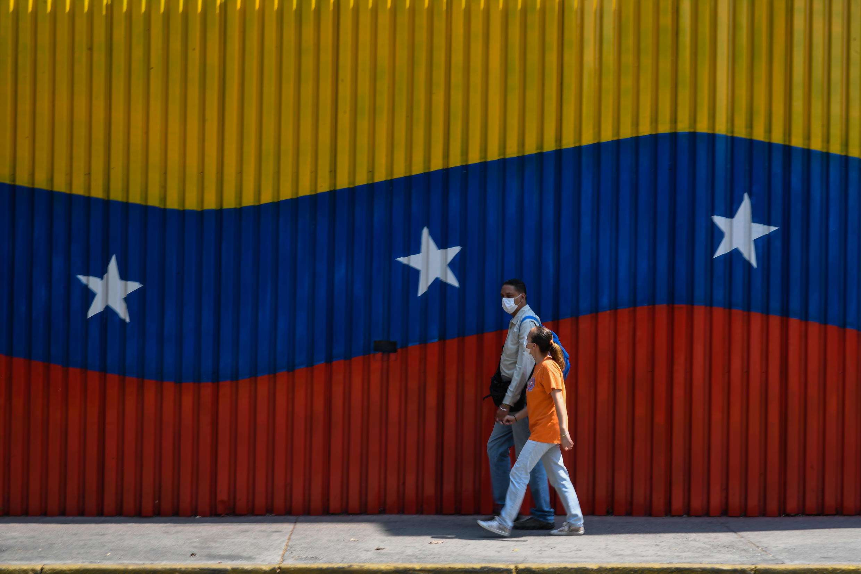 Esta imagen de archivo, tomada el 17 de abril de 2020 en Caracas, muestra a una pareja con mascarillas sanitarias delante de un mural pintado con la bandera de Venezuela
