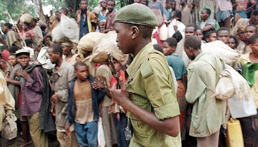 Un rebelle zaïrois de l'armée de Laurent-Désiré Kabila, soutenue par le FPR rwandais,  passe devant une foule de réfugiés hutus rwandais dans le camp de Biaro, près de Kisangani le 8 mai 1997.