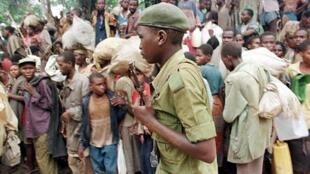 Un rebelle zaïrois de l'armée de Laurent-Désiré Kabila passe devant une foule de réfugiés hutus rwandais dans le camp de Biaro, près de Kisangani le 8 mai 1997.
