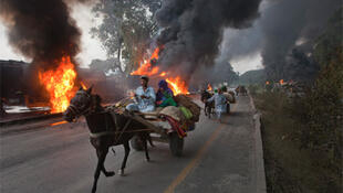 Locals pass burning Nato fuel tankers in Pakistan's Khyber-Pakhtunkhwa province.