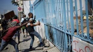 Des manifestants jettent de l'essence sur l'entrée des bureaux de la direction de l'immigration et de l'émigration à Port-au-Prince, le 28 octobre 2019.