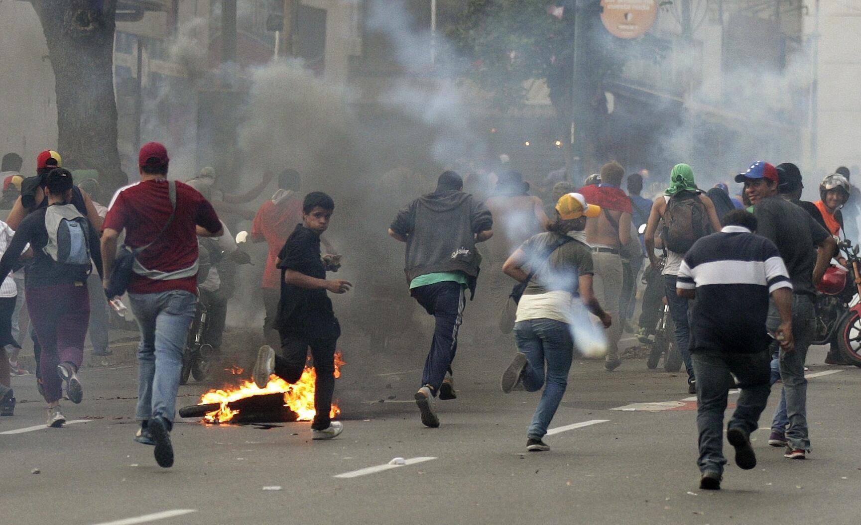 Les partisans d'Henrique Capriles dispersés à coup de gaz lacrymogène par la police, à Caracas, le 16 avril 2013.