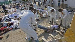 A l'hôpital général de Port-au-Prince, des milliers de corps sont transportés vers la fosse commune de la ville, le 14 janvier 2010.