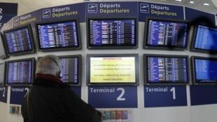 Passageiro diante dos paineis de informação do aeroporto Roissy-Charles de Gaulle