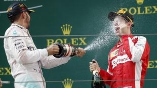 Lewis Hamilton sprays champagne at Sebastian Vettel of Germany on the podium at the Chinese Grand Prix on Sunday
