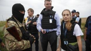Des responsables de l'équipe d'observateurs de l'OSCE s'entretiennent avec un combattant séparatiste pro-russe sur le site du crash.