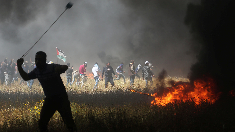 Palestinian demonstrators clash with Israeli troops at the Israel-Gaza border.