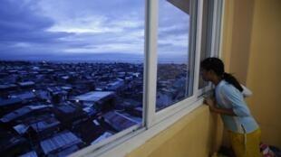 Une petite fille regarde à la fenêtre d'un centre d'évacuation à Manille, capitale des Philippines.