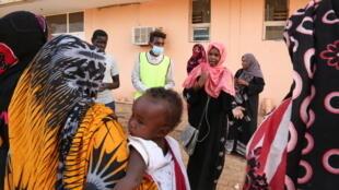 Suha et deux étudiants tentent de convaincre ce groupe de femmes de limiter les visites à l'hôpital pour éviter une propagation du coronavirus.