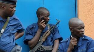Un policier anti-émeutes, l'oreille vissée au poste de radio, à Bujumbura, le 5 mai 2015.