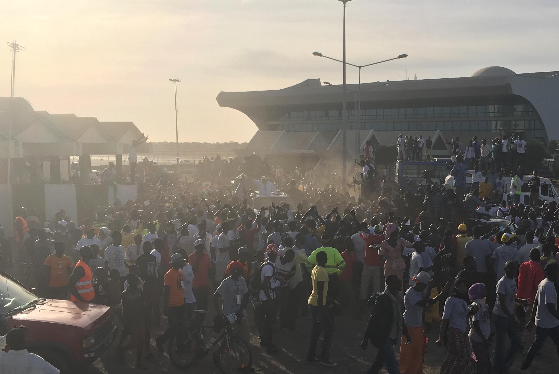 Le président élu de Gambie Adama Barrow (au centre) quitte l'aéroport de Banjul, entouré par la foule, le 26 janvier 2017.
