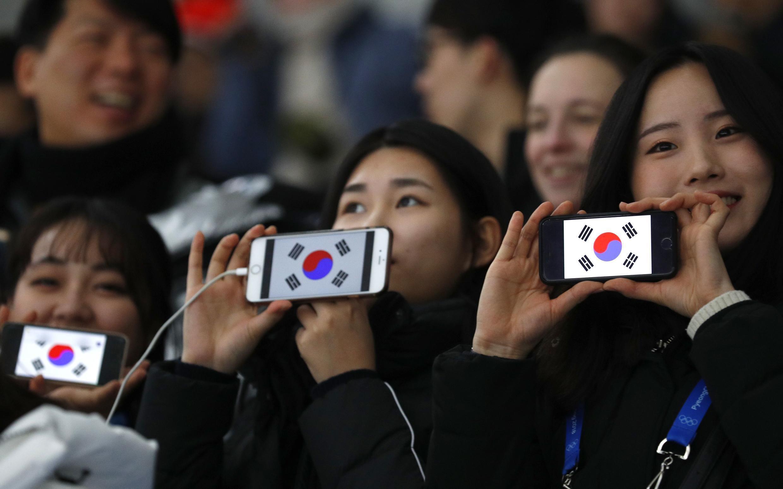 Des supporters sud-coréens affichent leur drapeau sur leur smartphone, lors d'une épreuve de patin à glace, aux Jeux olympiques de Pyeongchang, le 13 février 2018.