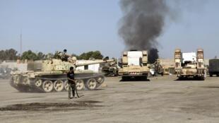 Des combats entre groupes armés dans le quartier général de la Brigade Qaqaa, à Tripoli, le 24 août 2014.