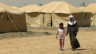 Una mujer, pariente de un hombre acusado de pertenecer al grupo Estado Islámico, camina en un campo en Bartella, al este de Mosul, Irak, el 15 de julio de 2017.