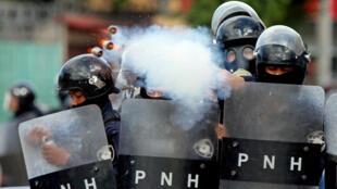 Un oficial de policía dispara gases lacrimógenos contra los manifestantes que protestaban por la juramentación presidencial de Juan Orlando Hernández, acusado de reelegirse mediante un presunto fraude.  Tegucigalpa, Honduras, el 27 de enero de 2018.