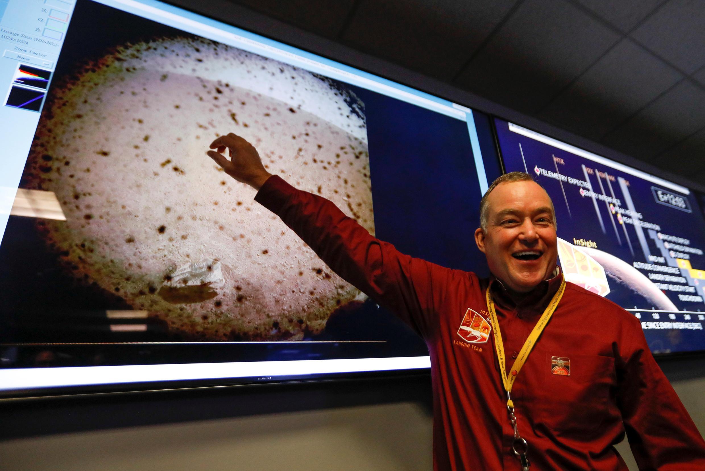Tom Hoffman ប្រធានគម្រោងបង្ហាញរូបថត ដែលយានអវកាសInSightបានថតបញ្ជូនមកវិញ នៅក្រោយចុះចតដោយជោគជ័យ កាលពីថ្ងៃចន្ទ។ រូបថតនៅមន្ទីរពិសោធន៍Jet Propulsion Laboratory (JPL) របស់ណាសា នៅ Pasadenaនៅរដ្ឋកាលីហ្វនីញ៉ា ថ្ងៃទី ២៦ វិច្ឆិកា ២០១៨