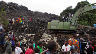Une pelleteuse s'active parmi les ordures et les décombres pour tenter de retrouver d'éventuels survivants.