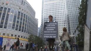 Uma mulher com um cartaz-cv procura emprego no bairro financeiro de Canary Wharf.
