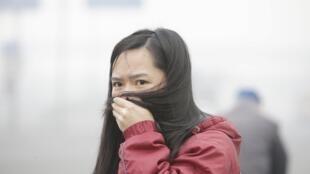 北京霧霾壓境,一女試用頭髮阻擋濃霧吸入。