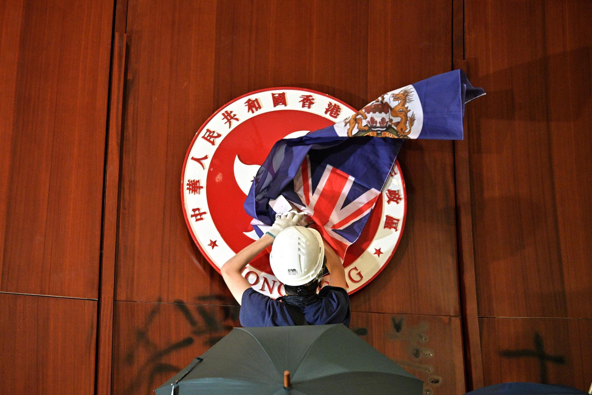 A protester tries to cover the Hong Kong flag with a British colonial flag during a break-in to the territorial parliament.