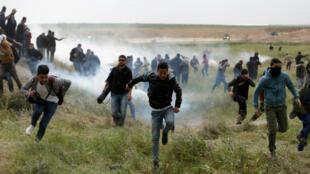 Des Palestiniens s'enfuient sous les grenades lacrymogènes lors d'une manifestation à la frontière entre Israël et la bande de Gaza, le 30 mars 2018 lors de la Journée de la terre 2018.