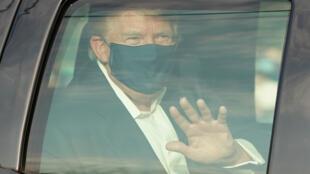 Le président américain Donald Trump salue ses partisans, lors d'une brève sortie en voiture de l'hôpital militaire Walter Reed, où il est soigné après avoir contracté le Covid-19, à Bethesda (Maryland), le 4 octobre 2020.