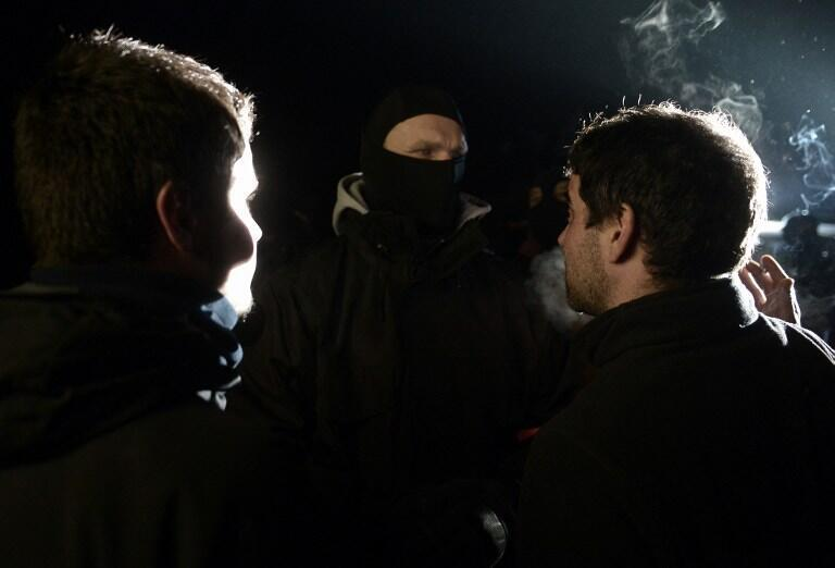 French police  face demonstrators in support of the arrested at the scene of the raid in Louhossoa on Friday night