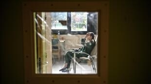 "A patient with mental disorders sits on a chair in her room at The Ville-Evrard Psychiatric Hospital in Saint-Denis, north of Paris on November 3, 2020. - After the consequences of the first confinement linked to Covid-19 are just starting to fall as psychiatrists at the mental health establishment of Ville-Evrard, in the Paris suburbs, fear a second ""psychiatric wave"". (Photo by Christophe ARCHAMBAULT / AFP)"