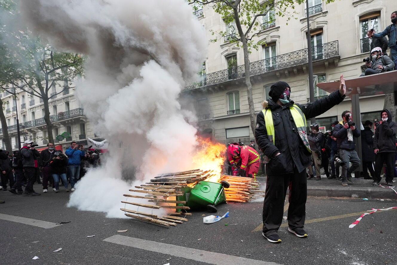 Um 'colete amarelo' gesticula perto de materiais incendiados durante os tradicionais protestos do 1º de maio, em meio ao surto da Covid-19 em Paris, França, em 1º de maio de 2021.