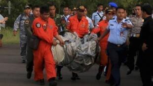 Les équipes de recherches et de secours transportent des débris de l'avion d'AirAsia, à quelque 160 km au sud-ouest de Pangkalan Bun, dans le centre de Kalimantan, le 30 décembre 2014.