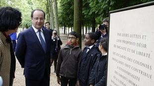 French President Francois Hollande speaks with children during a ceremony at the Luxembourg Gardens to mark the abolition of slavery and to pay tribute to the victims of the slave trade, in Paris, May 10, 2014.