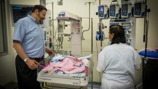 Le Pr. Jean-Jacques Aziria Rein, au chevet d'un enfant palestinien, dans le service de néo natalité de l'Hôpital Hadassa de Jérusalem en juillet 2014.