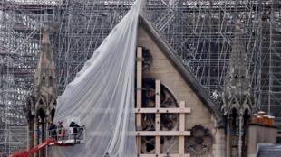 Les travailleurs procèdent à la délicate opération de démontage de l'échafaudage abimé par l'incendie, le 8 juin 2020.