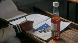 Une bouteille du «remède» malgache Covid Organics sur la table d'un écolier à  Antananarivo, le 23 avril 2020.