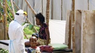 Funcionário do Hospital de Kenema, na província de Kenema, leste da Serra Leoa cuida de uma paciente afectada com o vírus Ebola, em agosto.