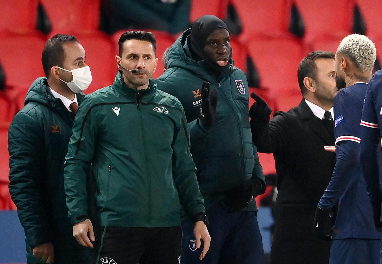 L'attaquant franco-sénégalais de l'Istanbul Basaksehir, Demba Ba (c), s'adresse à l'arbitre assistant roumain Sebastian Coltescu (2e g) lors du match de groupes de la Ligue des champions face au Paris-SG, au Parc des Princes, le 8 décembre 2020