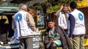 Des membres de Médecins du Monde viennent en aide à un homme à Grande-Synthe, le 11 avril 2017.