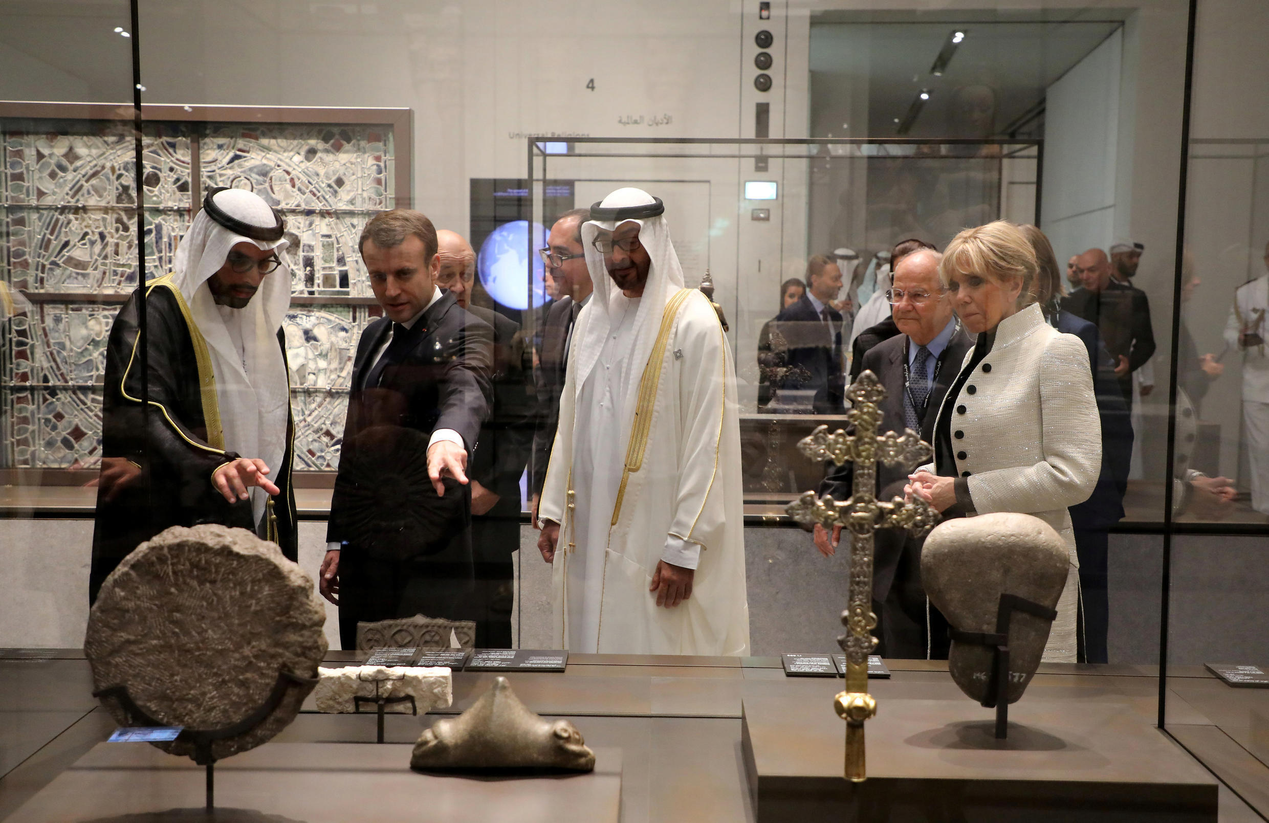 French President Emmanuel Macron (2ndL) and his wife Brigitte Macron (R) look at a piece of art as they visit the Louvre Abu Dhabi Museum during its inauguration in Abu Dhabi, UAE, November 8, 2017.