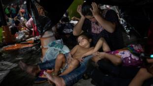 Uma imigrante de Honduras esfrega a cabeça enquanto se senta sob uma lona com sua filha, enquanto milhares da América Central a caminho dos Estados Unidos descansam em Huixtla, México, em 22 de outubro de 2018.