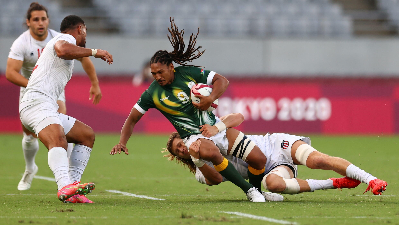 Le joueur de rugby sud-africain Justin Geduld plaqué par l'Américain Joe Schroeder, lors du tournoi des Jeux olympiques, le 28 juillet 2021 à Tokyo.