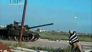 Imagen de un video realizado por un aficionado en que se ve un hombre arrojando piedras contra un tanque en la entrada de Deraa.